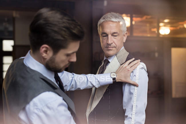 Tailor fitting businessman for suit in menswear shop — Stock Photo