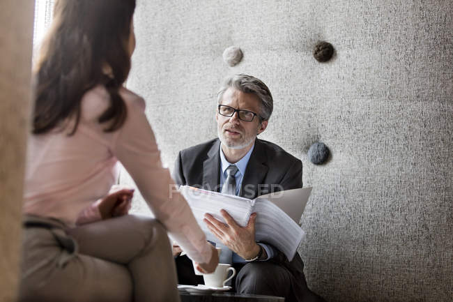 Businessman and businesswoman discussing paperwork — Stock Photo