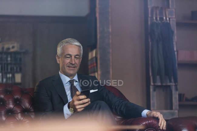 Geschäftsmann SMS mit Handy im Herrenmode shop — Stockfoto