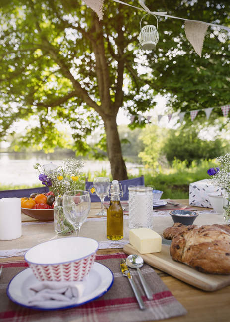 Bread and butter on patio table at lakeside — Stock Photo
