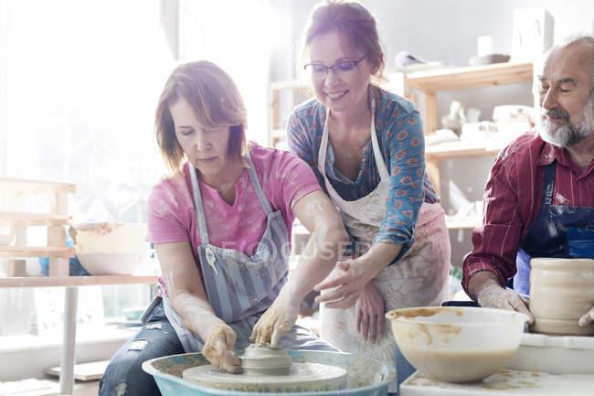 Teacher guiding mature student using pottery wheel in studio — Stock Photo