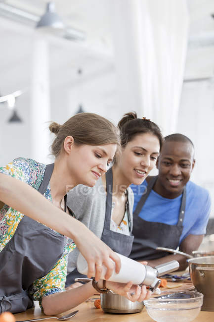 Friends enjoying cooking class in kitchen — Stock Photo