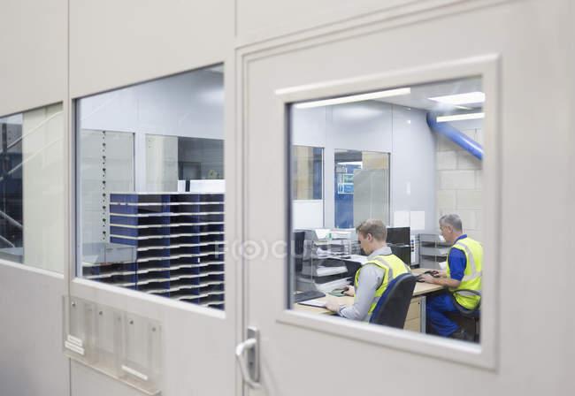Dos trabalhadores que trabalham em computadores no escritório da fábrica de aço — Fotografia de Stock