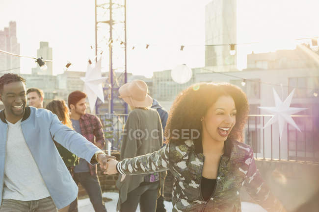 Playful young couple at rooftop party — Stock Photo
