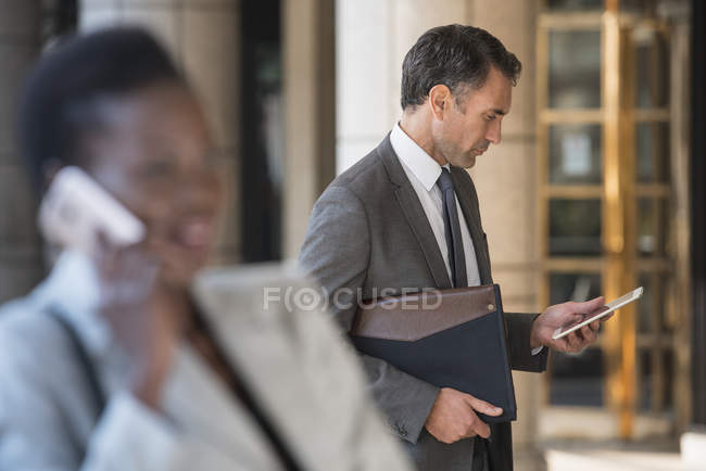 Corporate businessman using digital tablet outdoors — Stock Photo
