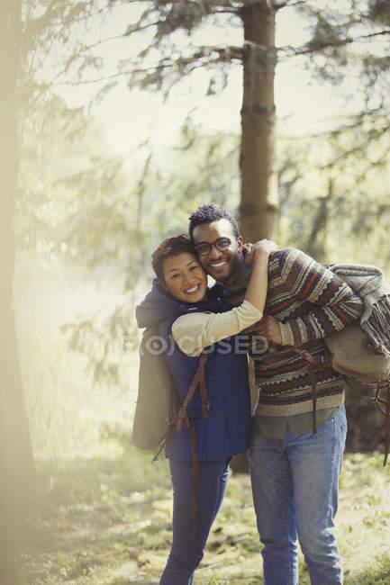 Retrato casal sorridente com mochilas caminhadas na floresta — Fotografia de Stock