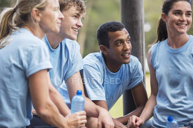 Équipe fatiguée se reposant et buvant de l'eau au camp d'entraînement — Photo de stock