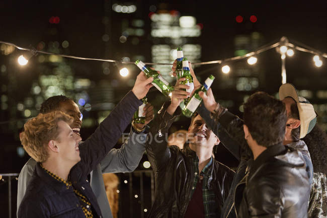 Young men toasting beer bottles at rooftop party — Stock Photo