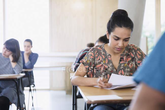 Grave studentessa universitaria che fa test alla scrivania in classe — Foto stock