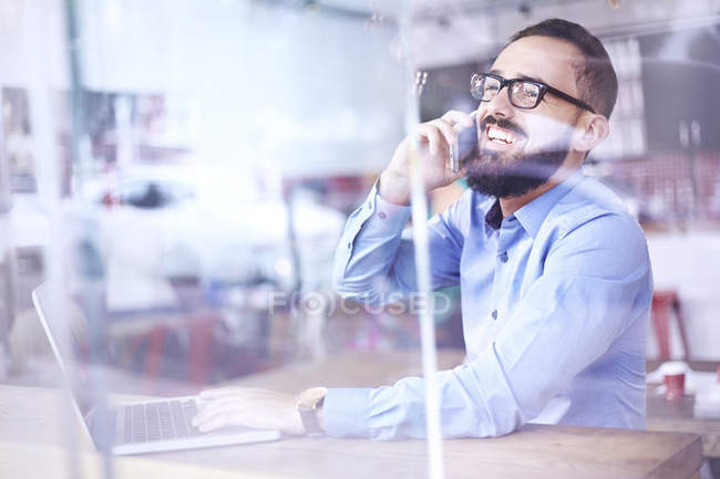 Laughing businessman talking on cell phone at laptop in cafe window — Stock Photo