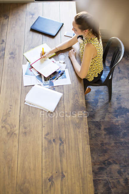 Creative businesswoman writing in notebook at table in office — Stock Photo