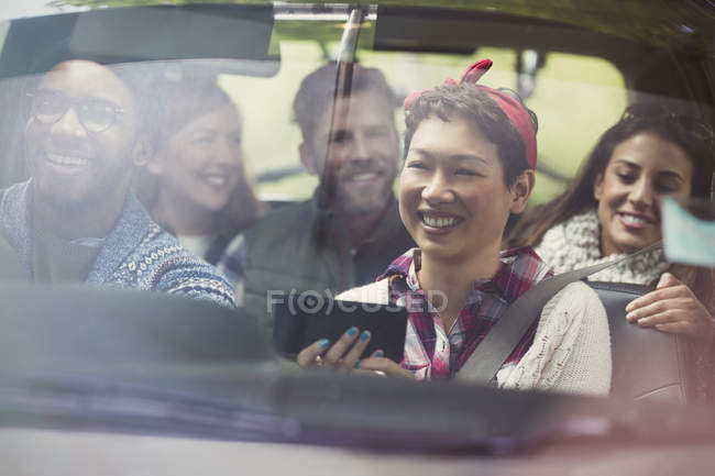 Smiling friends using GPS on smart phone riding in car — Stock Photo