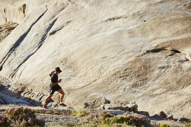 Male triathlete runner running on sunny rocky trail — Stock Photo