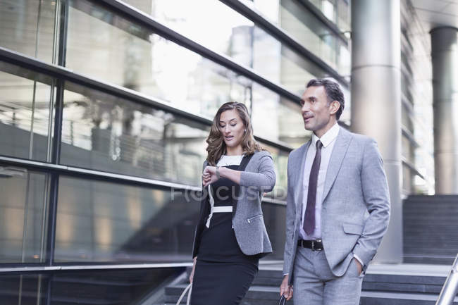 Corporate businesswoman checking wristwatch outside modern building — Stock Photo