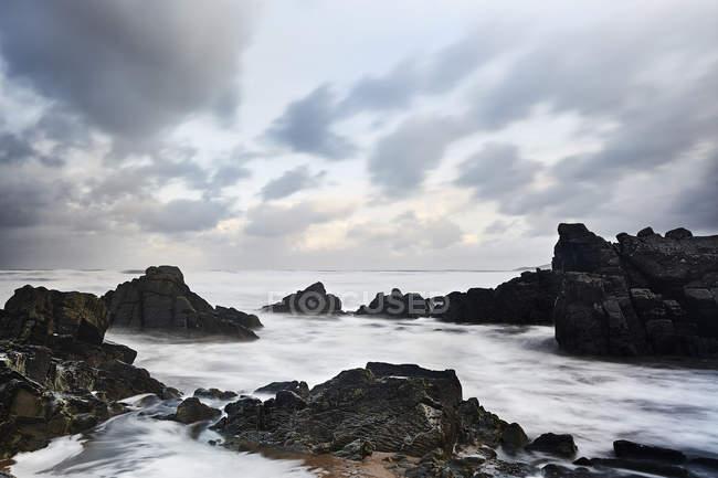 Роки и океан под облачным небом, Девон, Великобритания — стоковое фото