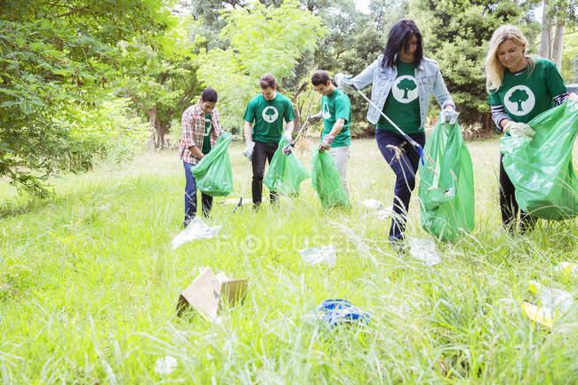 Des bénévoles écologistes ramassent des ordures sur le terrain — Photo de stock