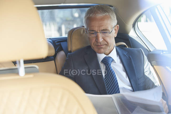 Businessman reviewing paperwork in back seat of town car — Stock Photo