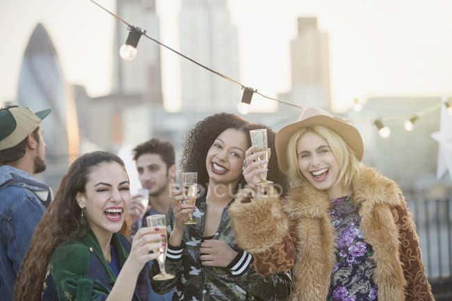 Retrato entusiasmado jovens mulheres bebendo champanhe na festa no telhado — Fotografia de Stock