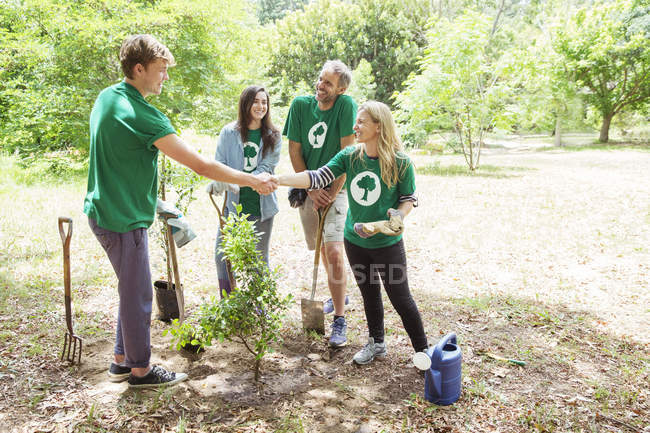 Environmentalist volunteers planting new tree and handshaking — Stock Photo