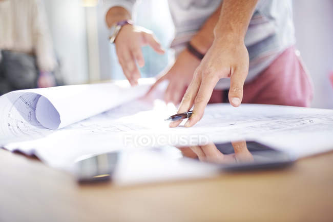 Cropped image of architects reviewing blueprints — Stock Photo
