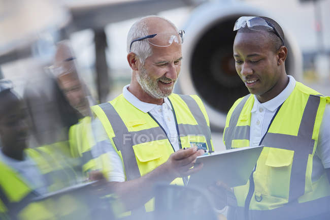 Air traffic control ground crew workers talking using digital tablet on airport tarmac — Stock Photo