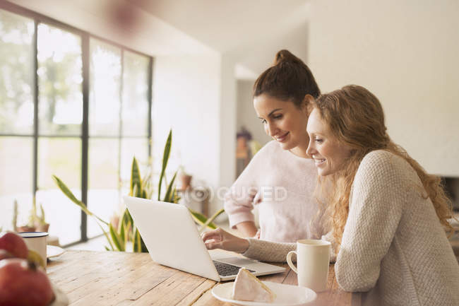 Women using laptop at dining table — Stock Photo