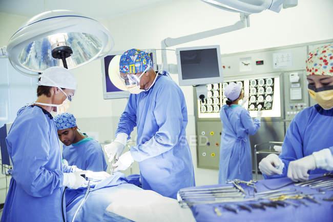 Chirurgiens opérant en salle d'opération — Photo de stock