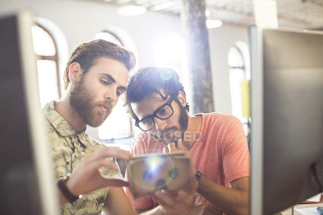 Creative businessmen reviewing proofs at computers in sunny office — Stock Photo