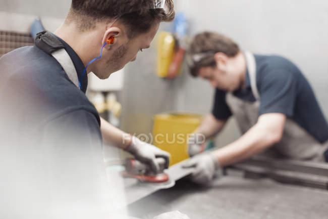 Workers sanding steel in steel factory — Stock Photo