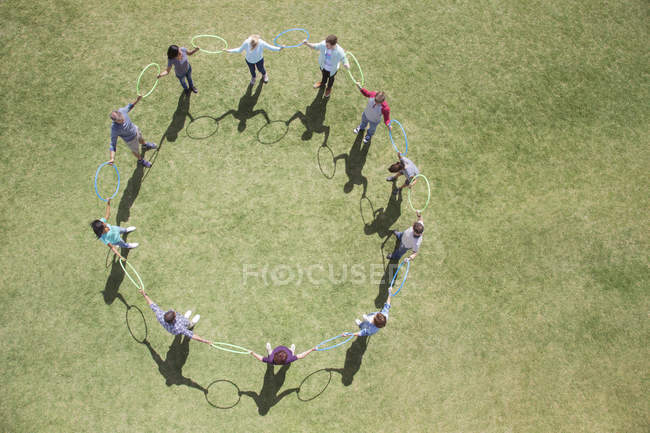 Team connected in circle by plastic hoops in sunny field — Stock Photo
