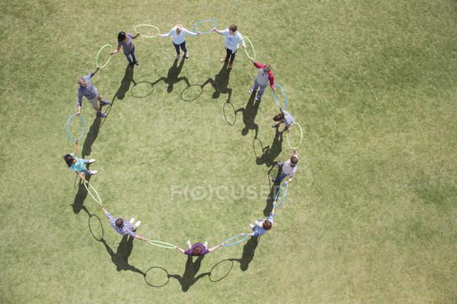 Equipe connectée en cercle par des cerceaux en plastique dans un champ ensoleillé — Photo de stock