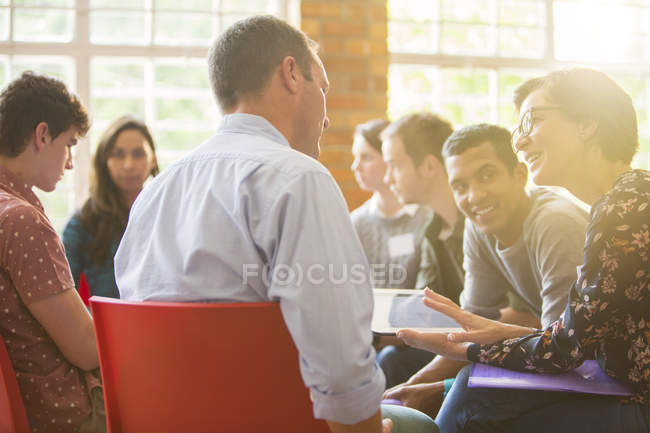 Woman with digital tablet speaking to man at group therapy session — Stock Photo