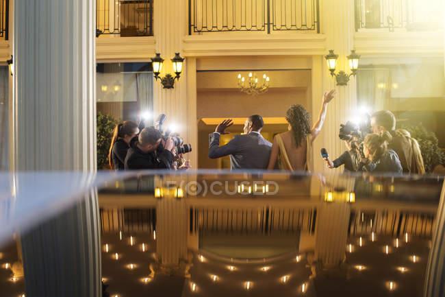 Зоряна пара прибувають і розмахуючи на папарацці фотографів на заході — стокове фото