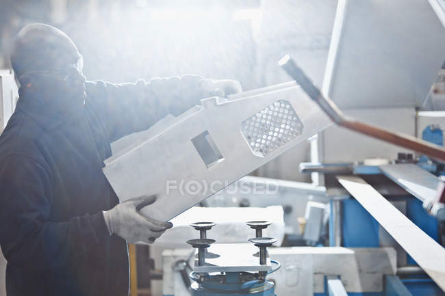Worker lifting piece in steel factory — Stock Photo