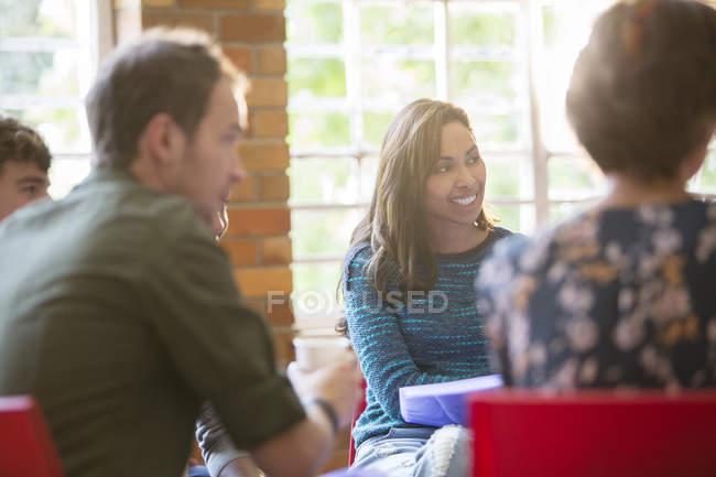 Mulher sorridente ouvindo em sessão de terapia de grupo — Fotografia de Stock