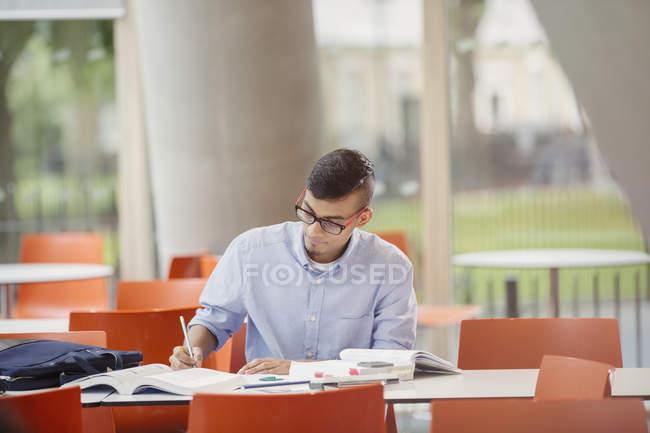 Étudiant masculin étudiant à table — Photo de stock