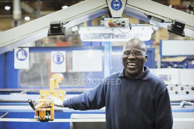 Портрет усміхнений працівника на машині в сталевих заводу — стокове фото