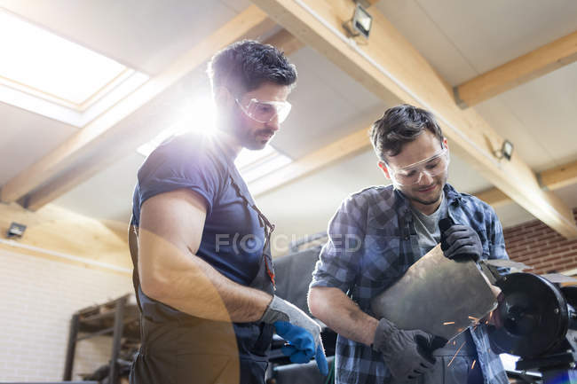 Métallurgistes utilisant ponceuse en atelier — Photo de stock