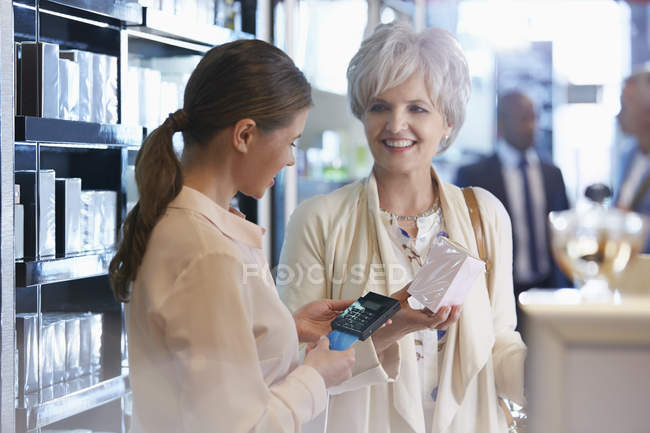 Woman buying perfume in shop from clerk with wireless credit card reader — Stock Photo