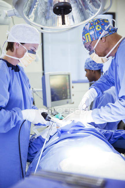Surgeons performing surgery in operating room at medical clinic — Stock Photo