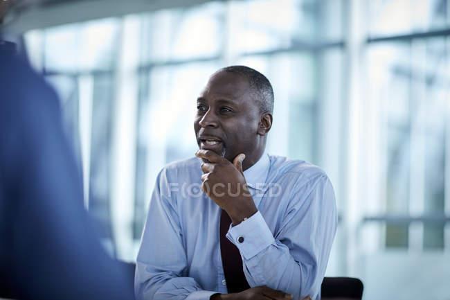Бизнесмен, прослушивания ищет прочь в заседании — стоковое фото