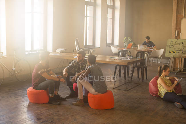 Casual business people meeting in circle in sunny office — Stock Photo