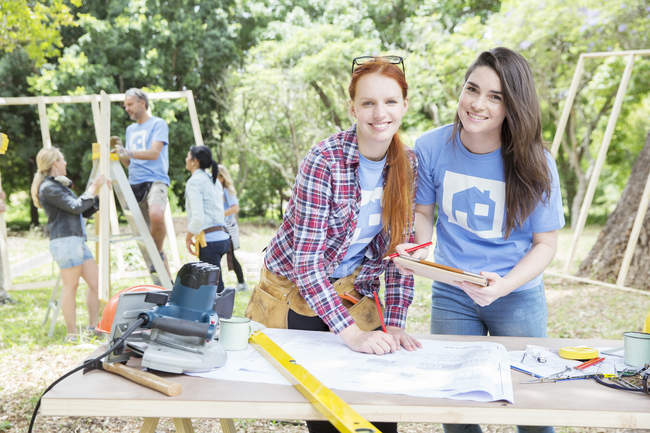 Portrait of smiling volunteers with digital tablet and blueprints at construction site — Stock Photo