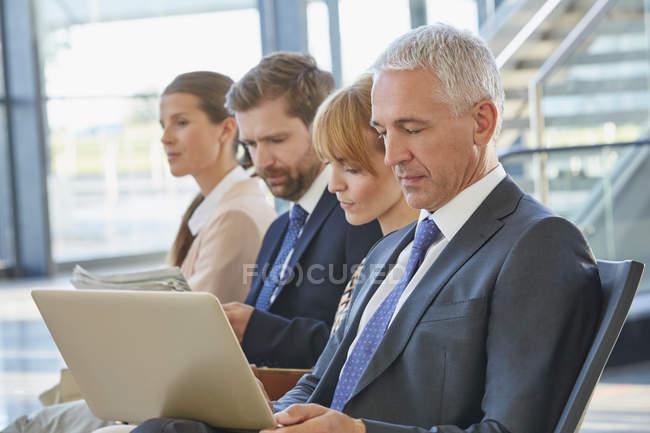 Homme d'affaires travaillant avec un ordinateur portable dans la zone de départ de l'aéroport — Photo de stock