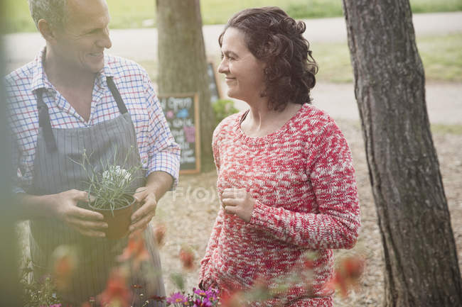 Plant nursery worker helping woman with potted flowers — Stock Photo
