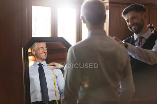 Homme d'affaires sur mesure au miroir dans un magasin de vêtements pour hommes — Photo de stock