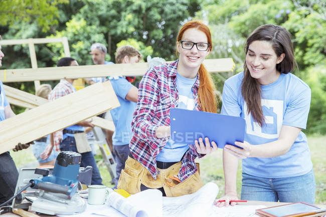 Volunteers with clipboard talking at construction site — Stock Photo