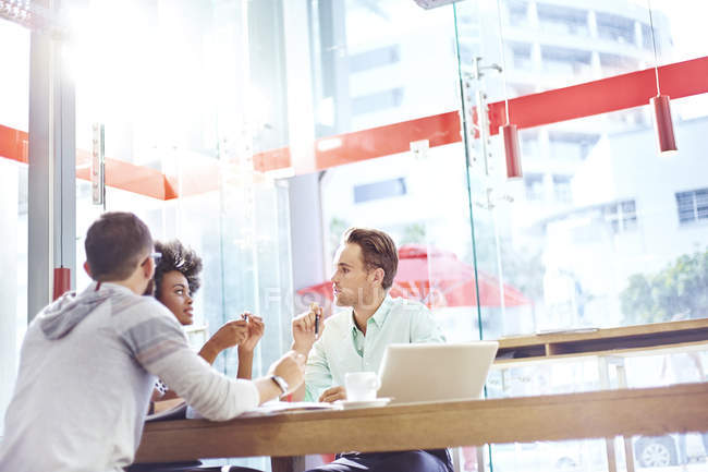 Business people meeting in sunny cafe — Stock Photo