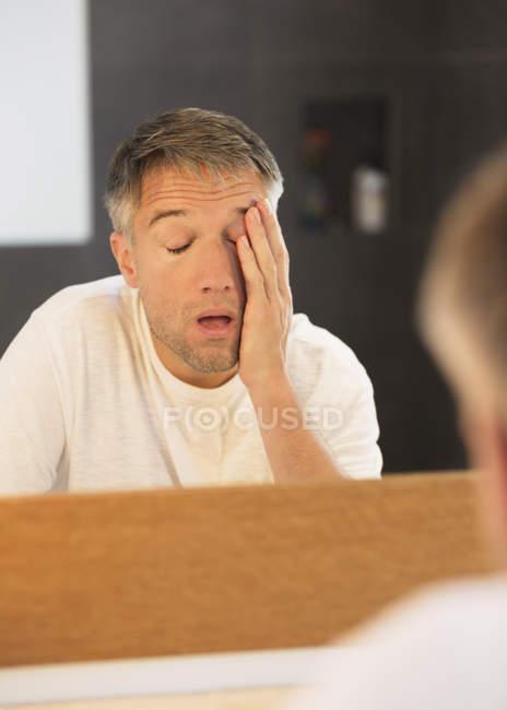 Hombre cansado con la cabeza en las manos en el espejo del baño - foto de stock