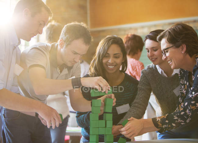 Business people stacking green blocks — Stock Photo